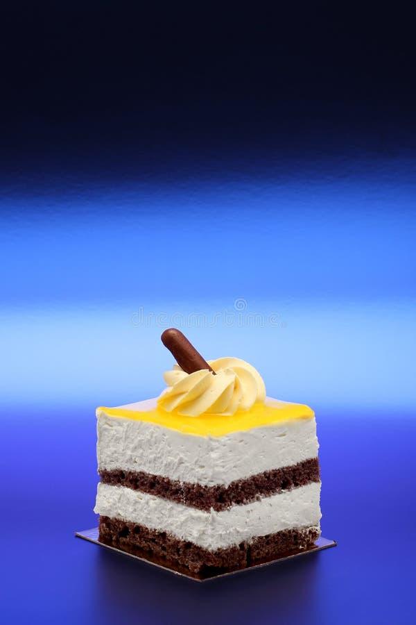Waniliowy i Czekoladowy tort na Kruszcowym Błękitnym tle obraz stock
