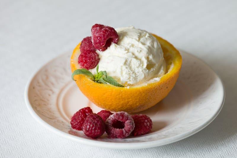 Waniliowy lody z malinką, lato deser Wyśmienicie sundae miarka w pomarańczowej połówce na białym talerzu obrazy royalty free