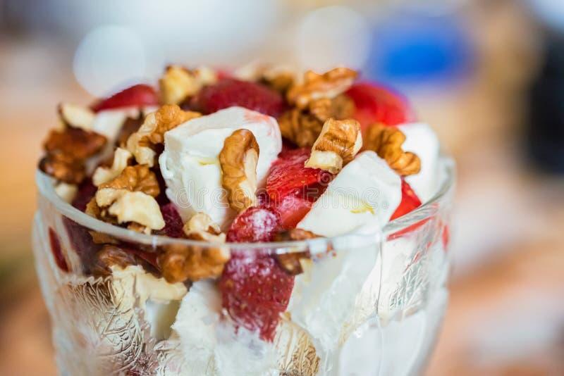 Waniliowy lody z truskawką i orzechem włoskim w pucharze na zamazanym tle obraz stock