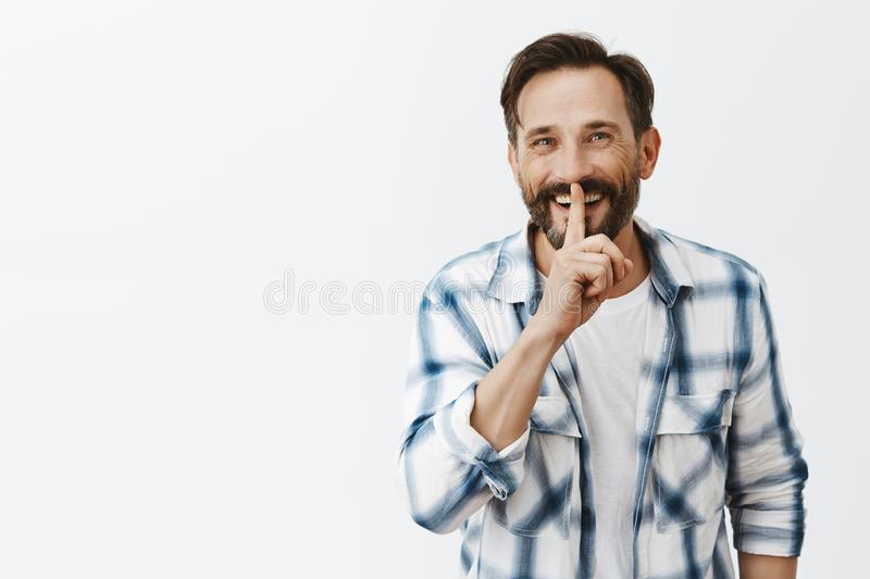 Wanna hear secret. Portrait of excited handsome adult man with beard and moustache smiling joyfully while making shush stock photo