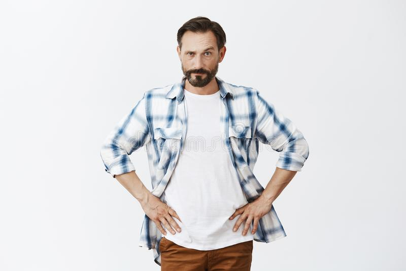 Wanna tell me something. Mad serious-looking upset father with beard, holding hands on waist, lifting eyebrow and royalty free stock photography