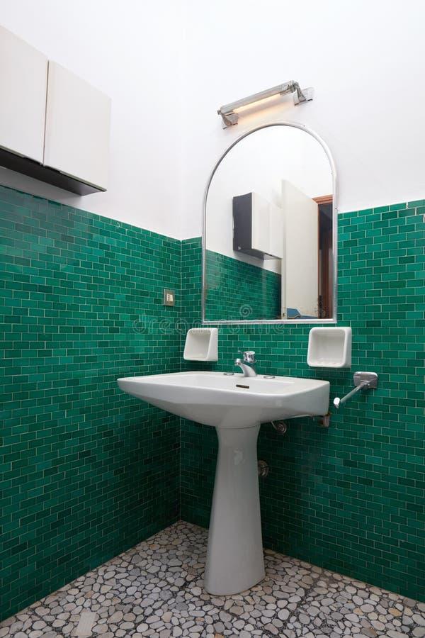 Wanne und Spiegel im grünen mit Ziegeln gedeckten Badezimmer, alter Wohnungsinnenraum stockfoto