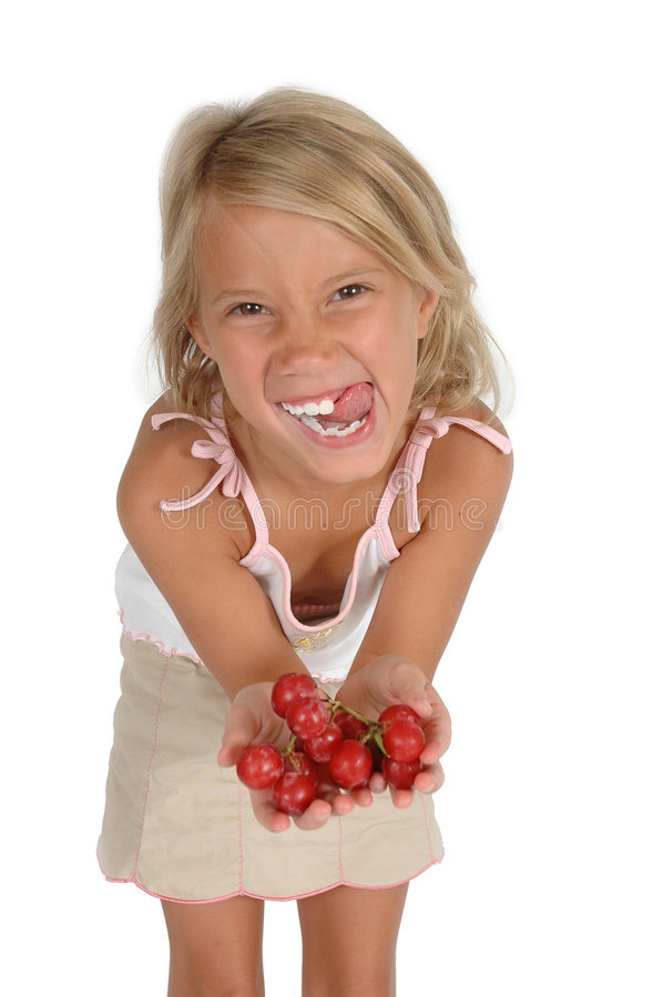 Want Some?. Little girl holds out hand to tempt you to eat grapes. Little child holds out healthy food choice royalty free stock photo