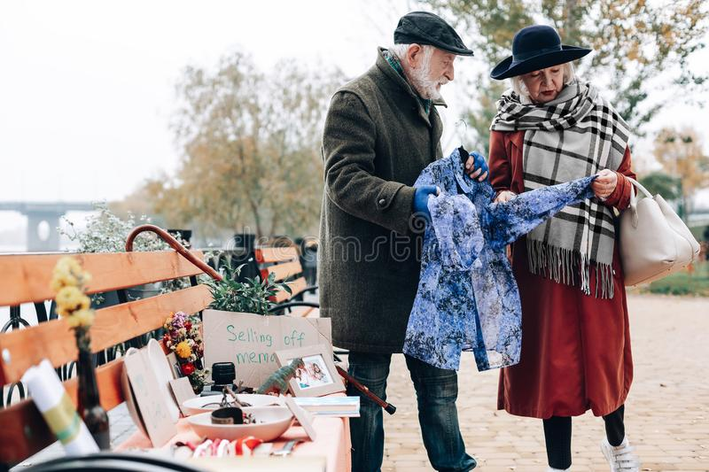 Attentive blonde woman looking at blue scarf stock photography