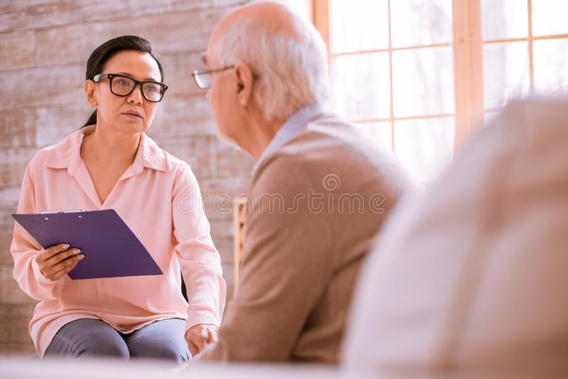 Kind young female talking to her patient stock photography