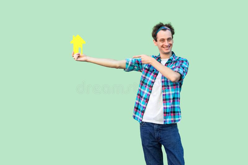 Want you own home? Happy young realtor man in checkered shirt holding yellow paper small house and propose you to planning new stock photos