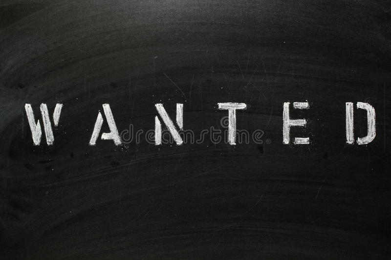 WANTED. The word WANTED in stencil letters on a blackboard stock photography