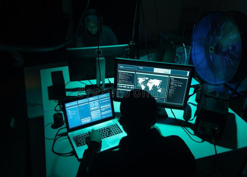Wanted hackers coding virus ransomware using laptops and computers. Cyber attack, system breaking and malware concept. stock image