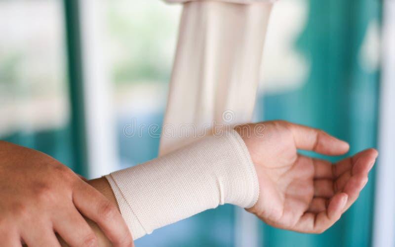 Wapen gekronkelde het verbinden hand en door verpleegster/de verwondingsgezondheidszorg en geneeskunde van de eerste hulppols royalty-vrije stock foto's