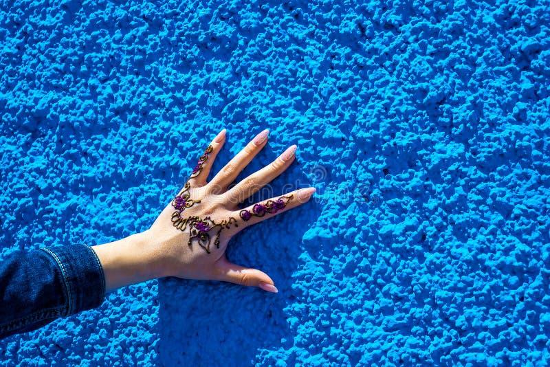 Wapen met een traditionele hennatatoegering op de achtergrond van de blauwe muur Rabat, Marokko stock afbeeldingen
