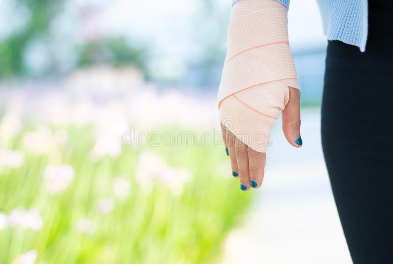 Wapensplinter, Verwonde vrouwelijke hand met lager lichaam Handverband met elastische stof royalty-vrije stock afbeeldingen