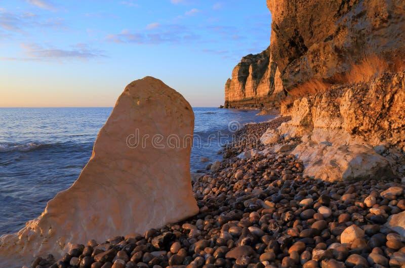 Wapień skała na otoczak plaży przy świtem zdjęcia stock