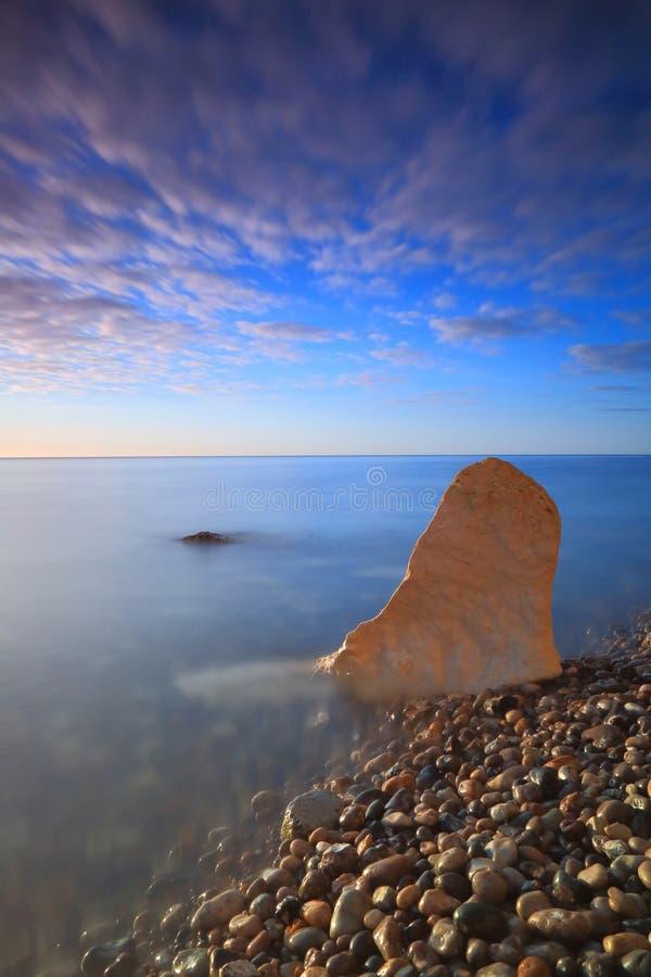 Wapień skała na otoczak plaży przy świtem fotografia stock