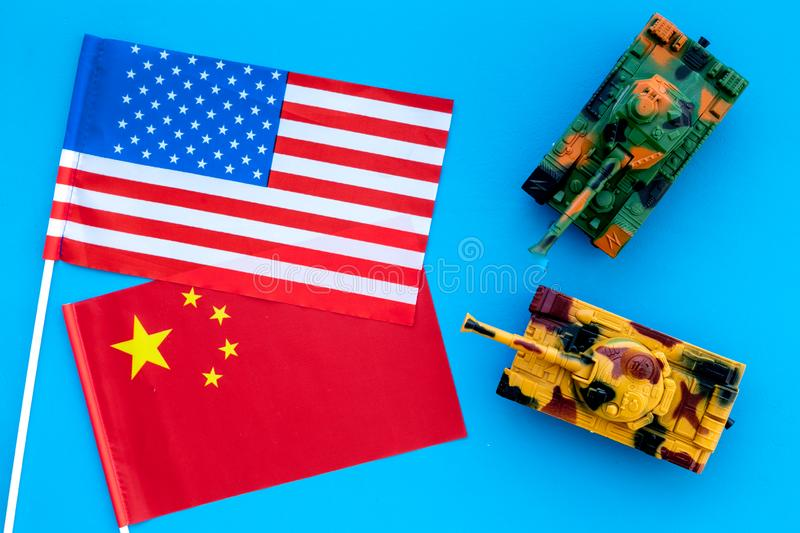 War, confrontation concept. China, USA. Tanks toy near chinese and american flag on blue background top view stock image