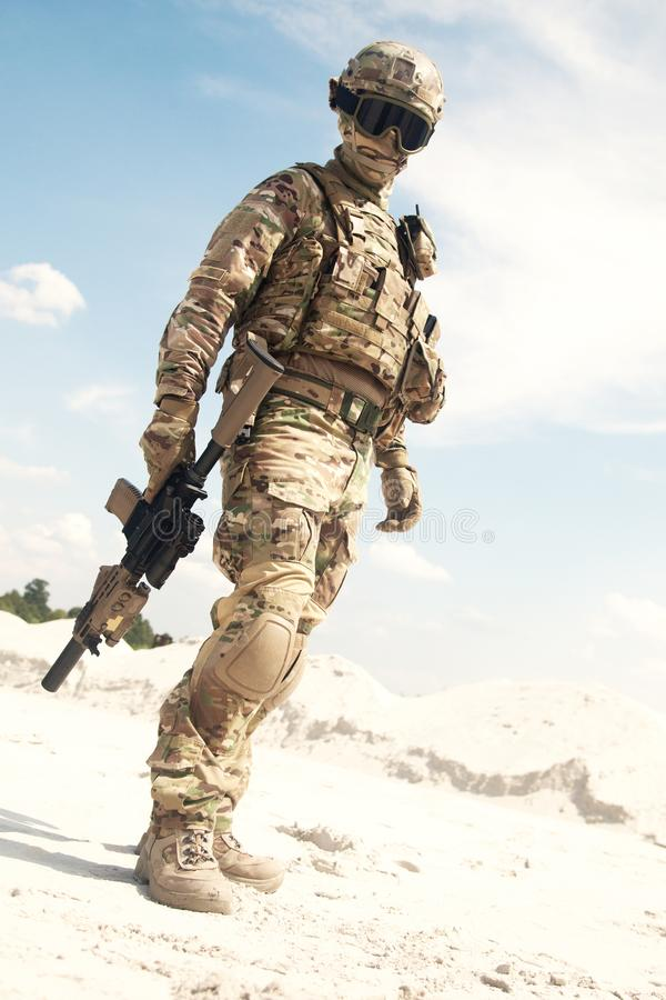 War games player equipped with tactical ammunition. Airsoft player, military games participant in U.S. army infantry camouflage uniform, tactical mask, helmet royalty free stock photos