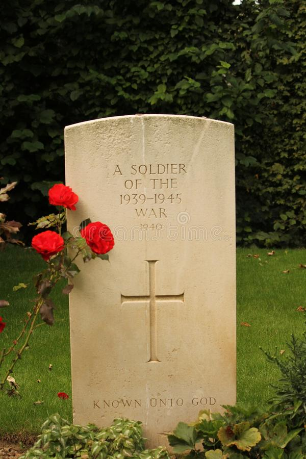A war grave closeup in normandy, france in summer. A war grave closeup and red poppies at a war cemetry in france royalty free stock photography