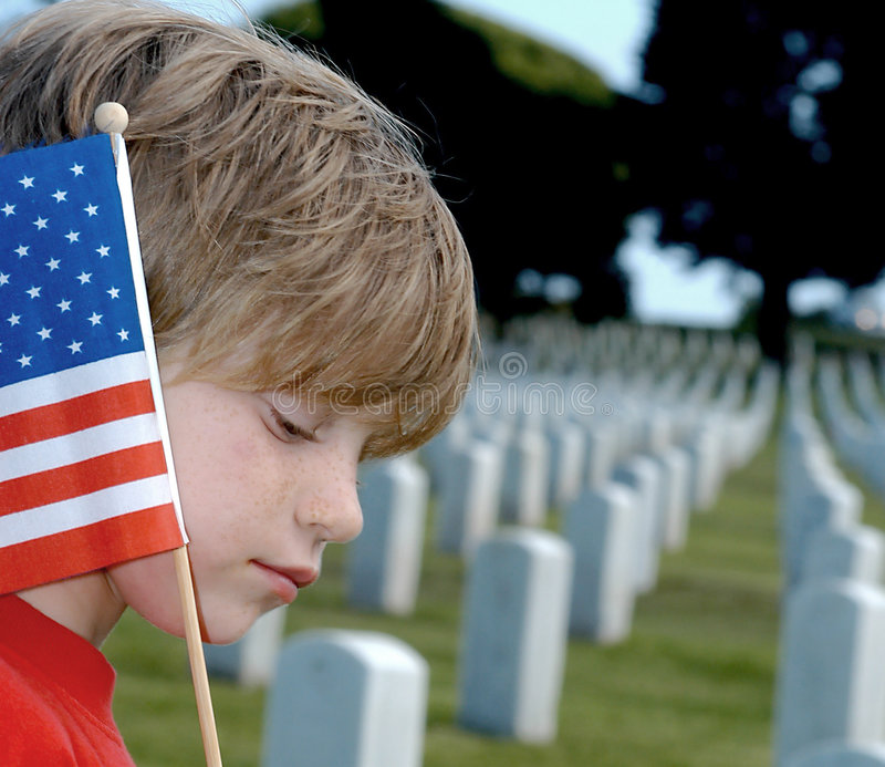 War and Loss. Bereaved child in a military cemetery with American flag royalty free stock image