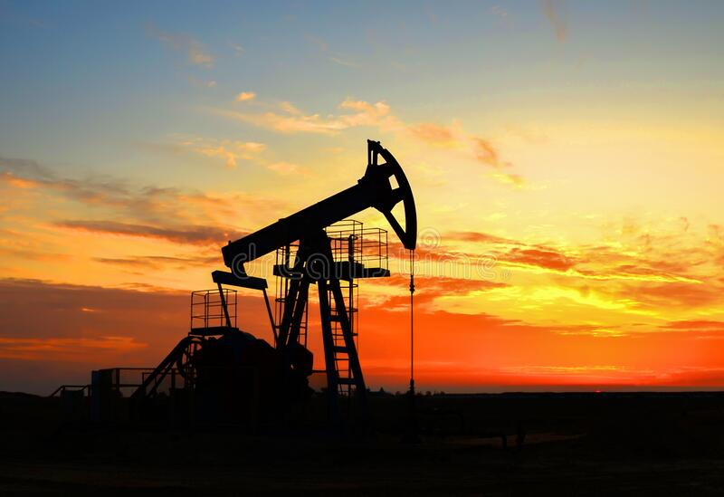 The war on oil prices caused by the coronavirus. Oil prices fall due to global crisis. Oil drilling derricks at desert oilfield. Crude oil production from the stock photography