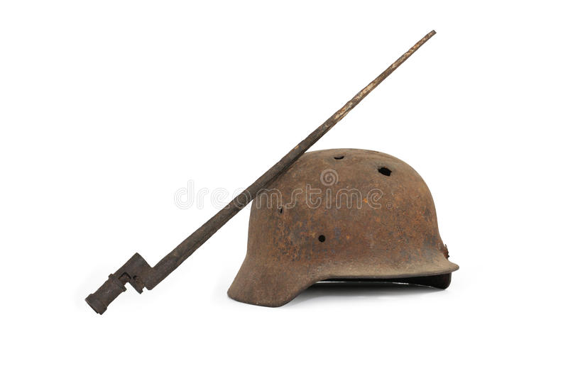 About War. Rusty and holed German military helmet and Russian bayonet on white background stock image