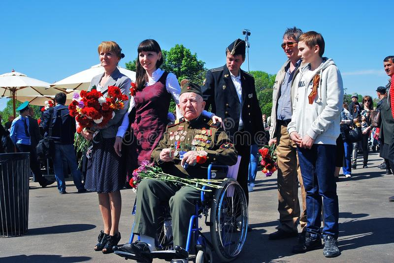 War veteran and young people pose for photos. royalty free stock image