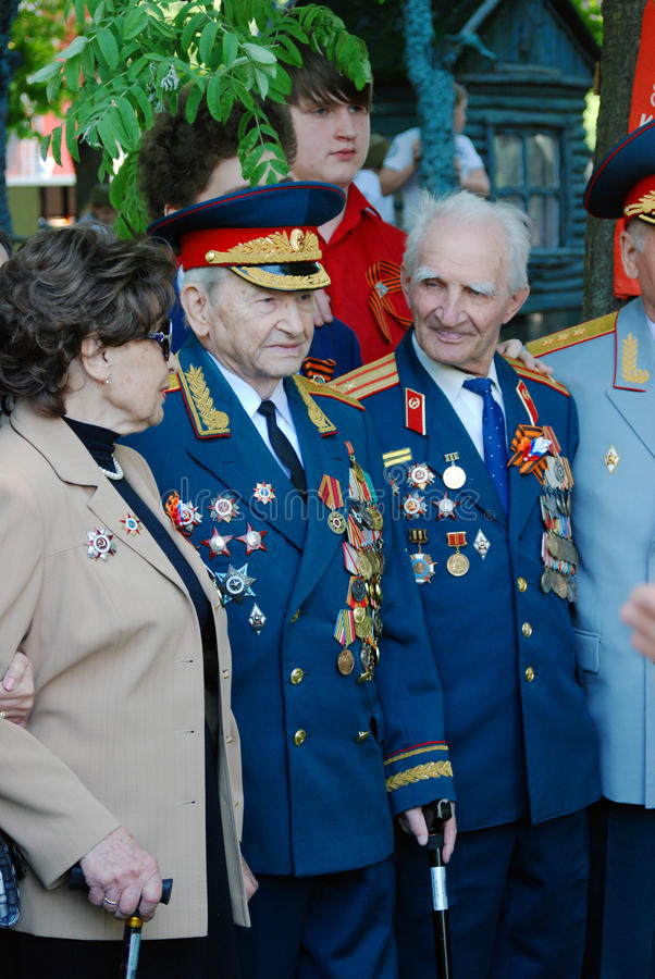War veterans, men and woman, pose for photos. MOSCOW - MAY 09, 2016: War veterans pose for photos. Victory Day celebration in Gorky park in Moscow stock photo