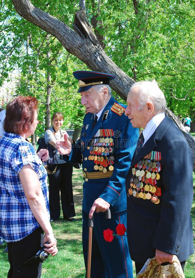 War veterans speak to a woman. In the park. Victory Day celebration in the Gorky park on May 09, 2013 in Moscow stock photos