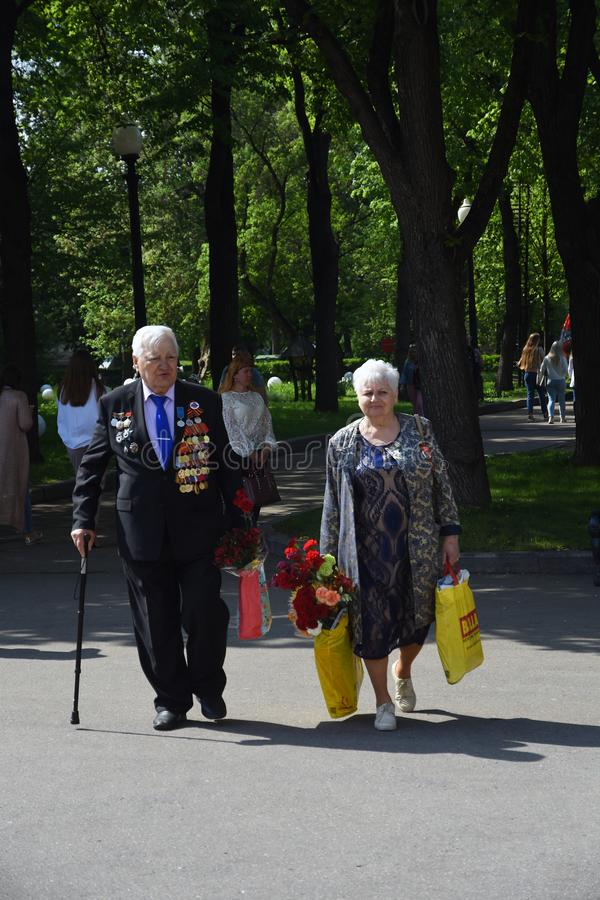 War veterans woman and man walks togerher. Gorky park in Moscow, Victory Day celebrations. May 09, 2019 stock images