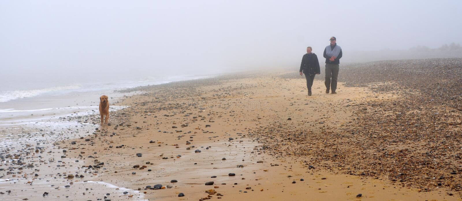 Couple Walking along Beach with Dog in the Fog. stock photo