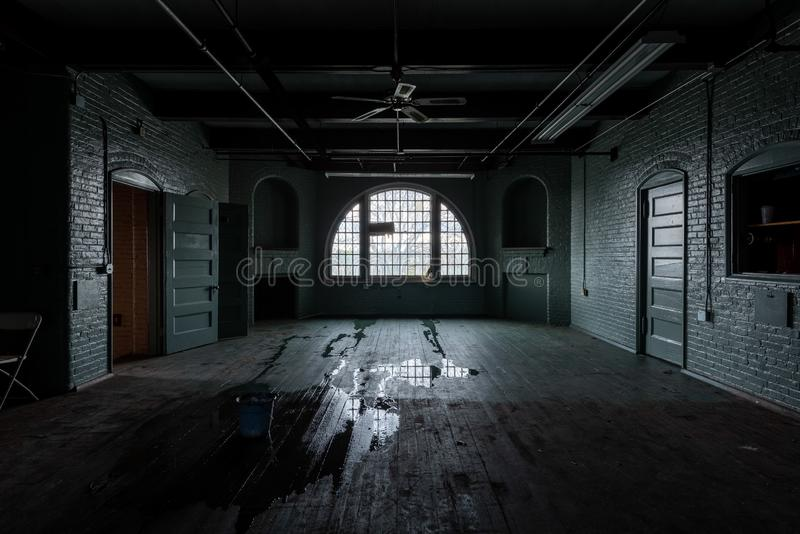 Ward Rooms - Abandoned Tewksbury State Hospital - Massachusetts. A solemn, quiet view of ward rooms inside an abandoned Tewksbury State Hospital building in stock image