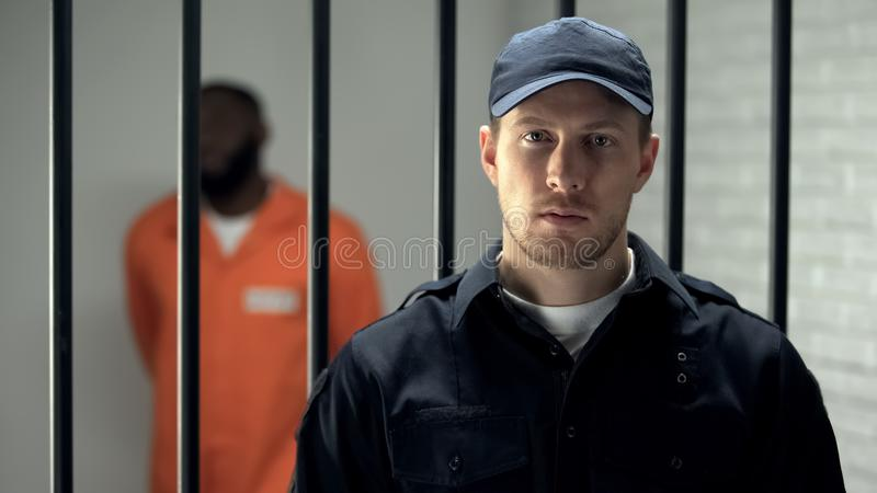 Warden looking at camera in prison, african american criminal on background royalty free stock photos