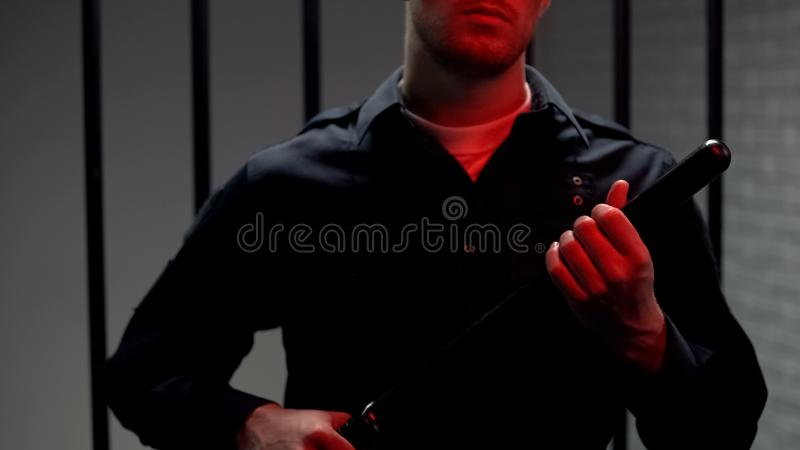 Warden standing near cell with truncheon, red lights, revolt crackdown, guard. Stock photo stock photo
