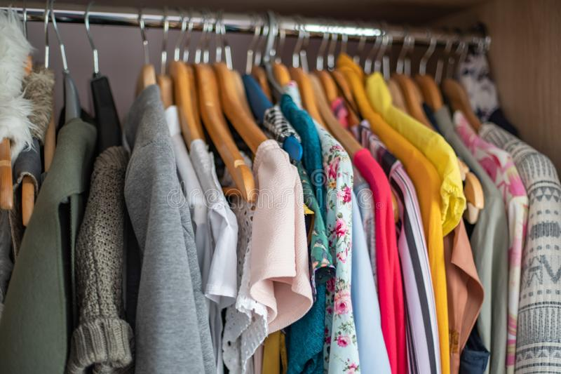 Wardrobe closet full of colorfull clothes in dressing-room. stock photography