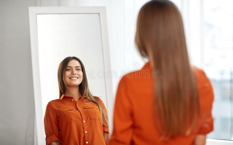 Happy woman choosing clothes at home wardrobe. Wardrobe, fashion, style and people concept - happy woman in orange shirt looking at mirror reflection at home or royalty free stock photos