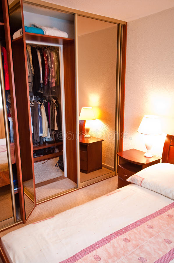 Wardrobe in modern bedroom. Clothes hung in open wardrobe with bed in foreground stock photos