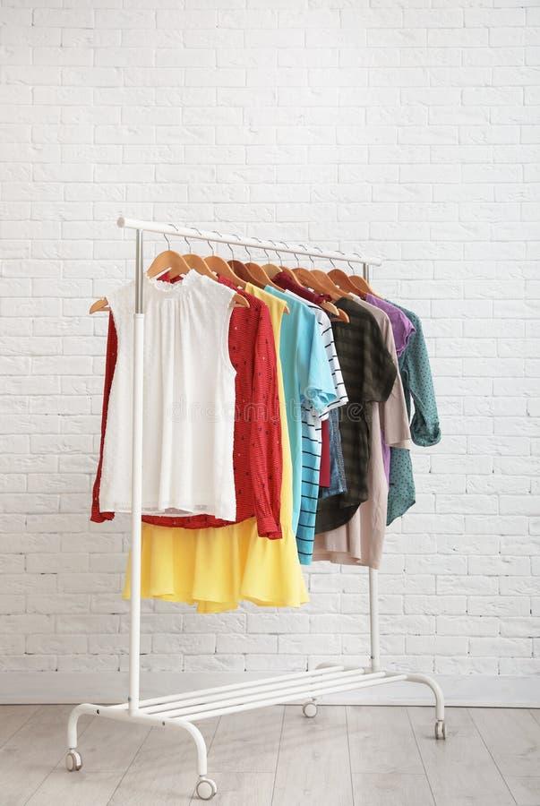 Wardrobe rack with stylish clothes near brick wall. Space for text. Wardrobe rack with stylish clothes near brick wall indoors. Space for text royalty free stock photos