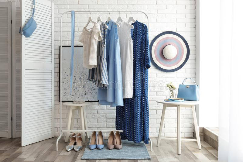 Wardrobe rack with women`s clothes and different shoes at white brick wall in. Room stock image
