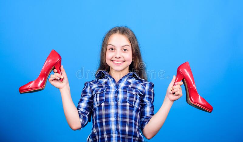 Wardrobe research. beauty and fashion. shoe shop and repair. shoe maker. happy childhood. small girl with stylish shoes. Happy child hold fashionable shoe royalty free stock images