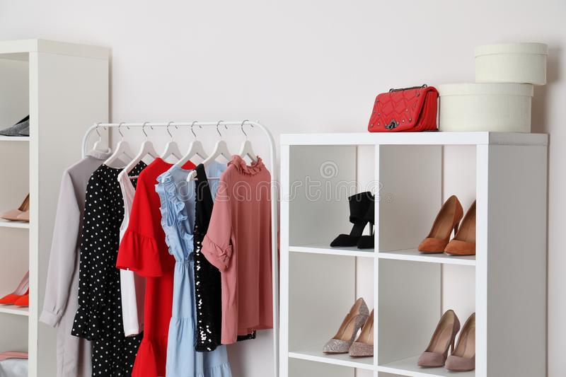 Wardrobe shelves with different stylish shoes and clothes indoors. Idea for interior. Design stock images