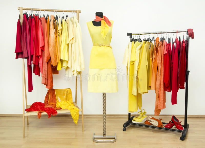 Wardrobe With Yellow Orange And Red Clothes Arranged On