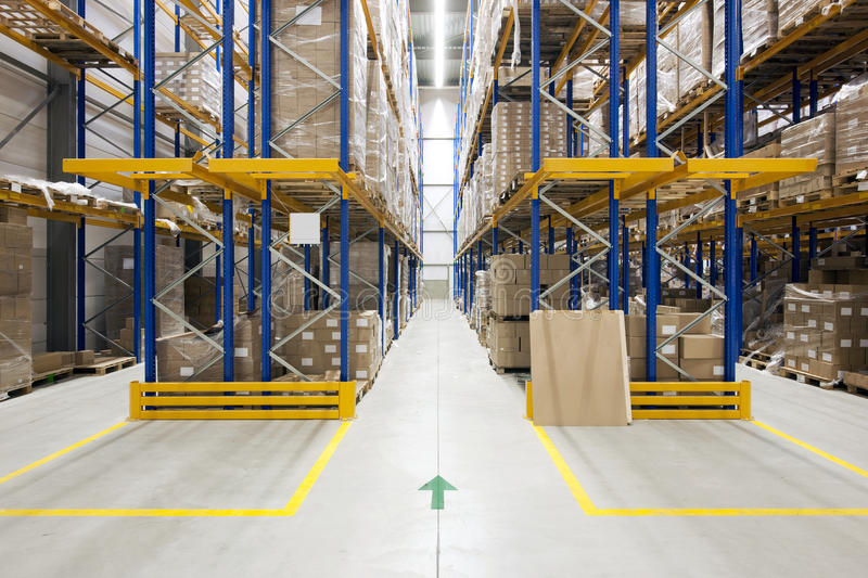Warehouse. With racks and shelves, filled with cardboard boxes, wrapped in foil on wooden pallets royalty free stock photos