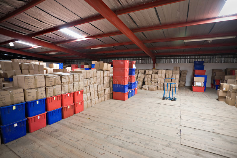 Warehouse. Hundreds of generic boxes with merchandise and trolley in a warehouse stock photo