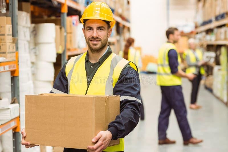 Warehouse arbetaren som ler på kameran som bär en ask arkivbild
