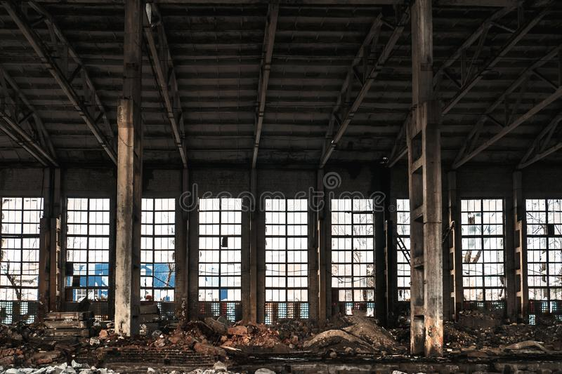 Warehouse with big windows, columns and debris of abandoned and ruined industrial factory building interior royalty free stock photo