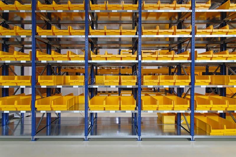 Warehouse bin trays. Yellow plastic bin trays at shelf in warehouse royalty free stock photography