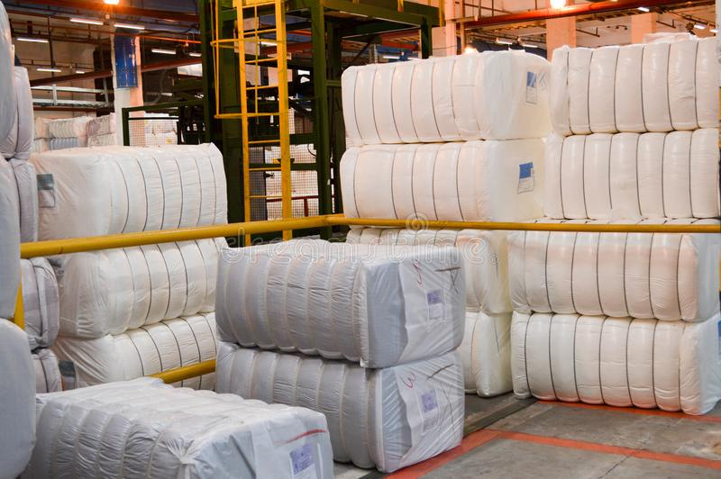 Warehouse with a bunch of huge, white bags with acrylic fiber stock photo