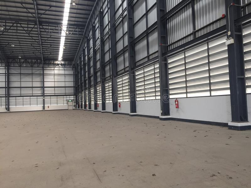 A warehouse is a commercial building for storage of goods. Logistics, perspective, plant, modern, architecture, iron, lamp, large, light, room, space royalty free stock photography