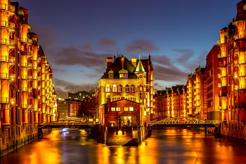 The Warehouse district Speicherstadt during twilight sunset in Hamburg, Germany. Illuminated warehouses in Hafencity quarter in royalty free stock image