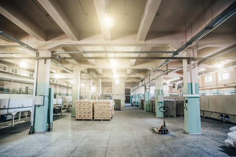 Warehouse in factory interior inside with boxes and other equipment. Toned royalty free stock image