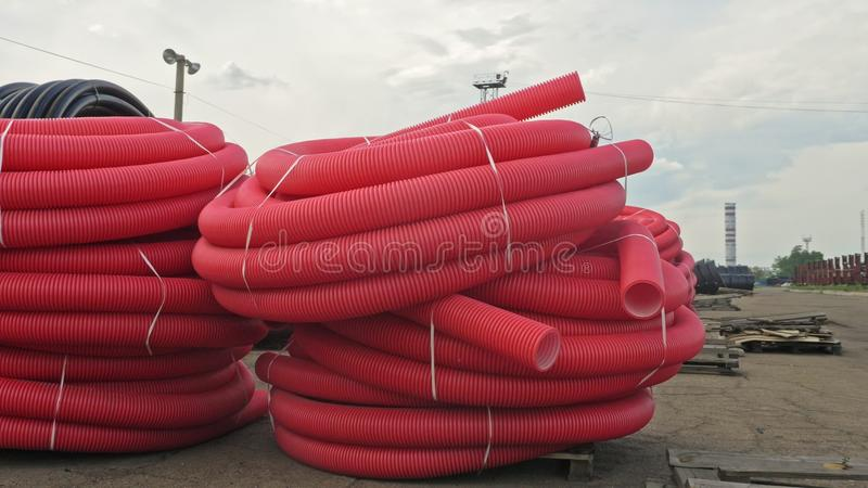 Warehouse of finished plastic pipes industrial outdoors storage site. Manufacture of plastic water pipes factory. stock images