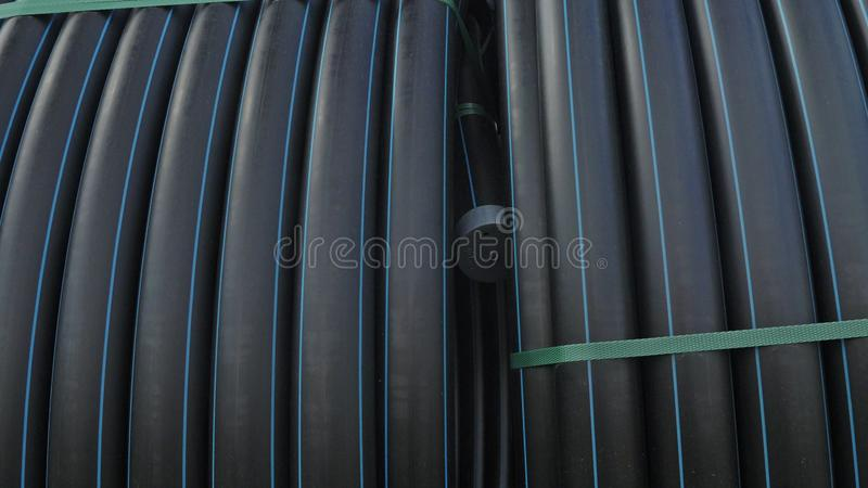 Warehouse of finished plastic pipes industrial outdoors storage site. Manufacture of plastic water pipes factory. stock photos
